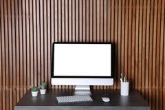 Современный монитор компьютера на столе против деревянной стены стоковое фото