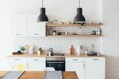 Современный новый светлый интерьер кухни с белыми мебелью и обеденным столом Стоковые Фото