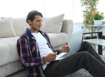 Современный парень при компьтер-книжка сидя на поле около софы Стоковые Фотографии RF