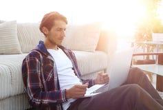 Современный парень при компьтер-книжка сидя на поле около софы Стоковые Изображения RF