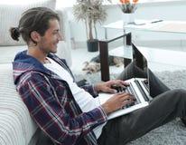 Современный парень при компьтер-книжка сидя на поле около софы Стоковое Фото