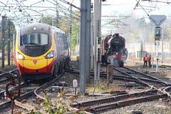 Современный поезд Pendolino проходя старый поезд пара Стоковое фото RF
