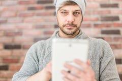 Современный прибор планшета удерживания парня против кирпичной стены стоковая фотография rf