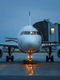Современный самолет припаркованный на стробе авиапорта сумрак Стоковые Фото