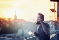 Современный счастливый молодой человек с вапоризаторами, дымом и пузырями потехи бороды на террасе В предпосылке, заход солнца ве Стоковое фото RF