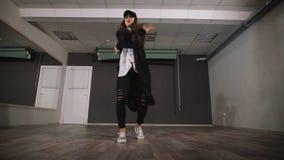 Современный танец танцев маленькой девочки в черных одеждах Танцор делает быстрые и активные движения оружий и ноги во время ее видеоматериал
