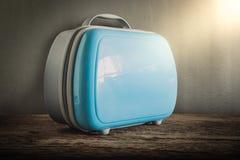 Современный туристский багаж на деревянной столешнице против стены grunge Стоковая Фотография RF