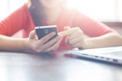 Современный умный телефон в руках ` s женщины Молодая женщина держа электронное устройство, используя свободное Wi-Fi, наблюдая в Стоковые Фотографии RF