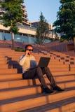 Современный фрилансер говоря на смартфоне и используя ноутбук пока сидящ на шагах перед организацией бизнеса на заходе солнца стоковые фотографии rf