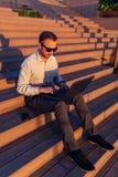Современный фрилансер сидя на лестнице и работая на ноутбуке стоковая фотография