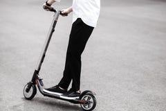 Современный человек в стильном черно-белом обмундировании ехать электрическое sco стоковое изображение rf