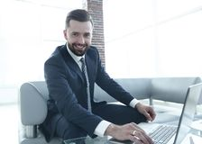 Современный человек работая на компьтер-книжке в лобби офиса Стоковые Изображения RF