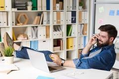 Современный человек ослабляя на проломе в офисе Стоковое Фото