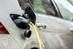 Современный электрический автомобиль поручая с силовым кабелем стоковая фотография rf