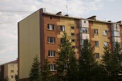 Современный 5-storeyed дом с квартирами Оно было покрашено в красных, оранжевых и белых цветах Стоковая Фотография