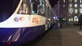 Современный tramcar покидая трамвайная остановка, активное движение в городе городском на ноче акции видеоматериалы