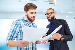 2 современных бизнесмена говоря и смотря документы Стоковые Фотографии RF