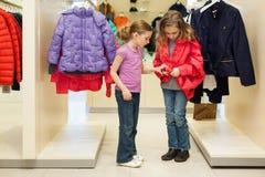 2 современных девушки пробуют дальше одежды в магазине Стоковое фото RF