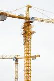2 современных желтых крана конструкции над небом Стоковое Фото