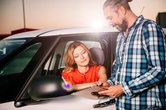 Согласование проката автомобиля чтения женщины стоковое изображение