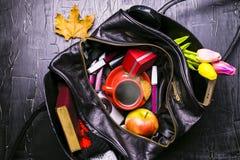 Содержание женской сумки Цветки, губная помада, камера, кофе, печенья, шарики Темная предпосылка Стоковые Изображения
