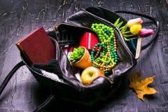 Содержание женской сумки Цветки, губная помада, камера, кофе, печенья, шарики Темная предпосылка Стоковая Фотография RF