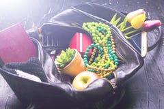 Содержание женской сумки Цветки, губная помада, камера, кофе, печенья, шарики Темная предпосылка Стоковые Изображения RF