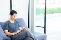 содержание средств массовой информации бизнесмена наблюдая в таблетке сидя на софе дома Стоковое Изображение