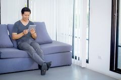 содержание средств массовой информации бизнесмена наблюдая в таблетке сидя на софе дома Стоковые Фото