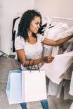 Содержимая женщина исследуя стильную одежду в магазине стоковая фотография