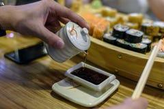 Соевый соус мужской руки лить для суш на японском ресторане стоковая фотография
