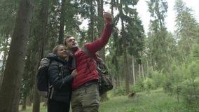 Соединенный парами технологии молодыми hikers используя smartphone для видео- звонка в лесе деля опыт отключения сток-видео