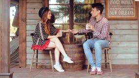 Соедините выпивая чай/кофе в Диких Западах, в западном доме Девушка в шляпе с длинными волосами Улыбка девушки и мальчика, смеясь сток-видео