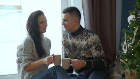 Соедините выпивая чай около рождественской елки видеоматериал