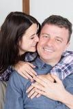 соедините выражать их влюбленность поцелуем в кресле дома стоковое изображение