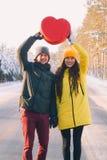 Соедините в любов держа большое красное сердце на предпосылке леса зимы снежного стоковая фотография