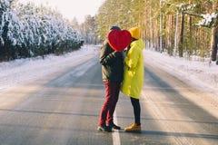 Соедините в любов держа большое красное сердце на предпосылке леса зимы снежного стоковые изображения