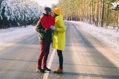 Соедините в любов держа большое красное сердце на предпосылке леса зимы снежного стоковое фото