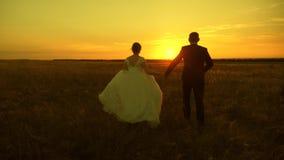 Соедините в любов держа руки идет к заходу солнца Счастливые человек и женщина бегут на заходе солнца Пары в любов на медовом мес сток-видео