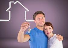 Соедините держать ключевой с значками дома перед виньеткой Стоковая Фотография