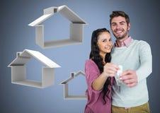 Соедините держать ключевой с значками дома перед виньеткой Стоковое Изображение