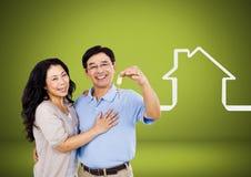 Соедините держать ключевой с значком дома перед виньеткой Стоковые Фотографии RF
