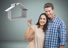 Соедините держать ключевой с значком дома перед виньеткой Стоковая Фотография