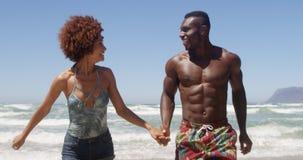 Соедините держать руки и бежать совместно на пляже 4k сток-видео