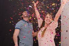 Соедините дуя confetti в воздухе изолированном над серым цветом Стоковые Изображения