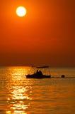 Соедините ехать шлюпка педали на море на заходе солнца Стоковые Фото
