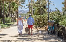 Соедините идти их собака вдоль прогулки в Марбелье в стоковые фотографии rf