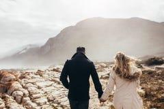 Соедините идти через скалистую береговую линию на зимний день Стоковая Фотография