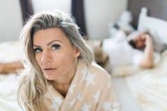 Соедините иметь кризис в кровати Женщина сидя на крае кровати стоковые фотографии rf