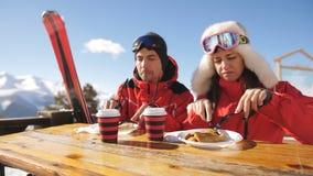 Соедините лыжников на горе имея обед в ресторане outdoors Лыжный курорт видеоматериал